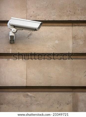 CCTV camera on stone-clad wall - stock photo
