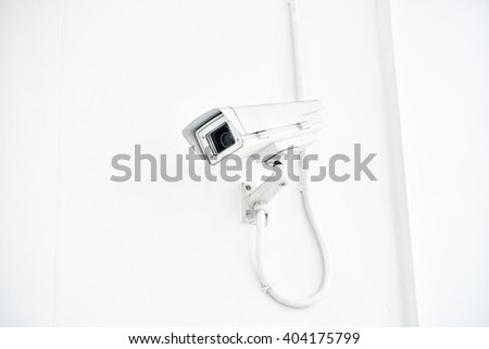 CCTV camera on white wall. - stock photo
