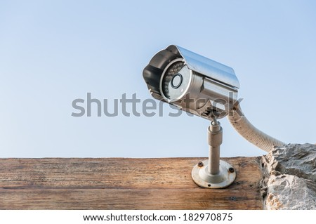 CCTV camera on wooden wall against sky