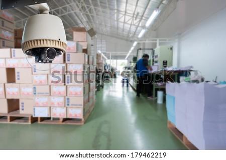 CCTV Camera Operating inside warehouse or factory - stock photo