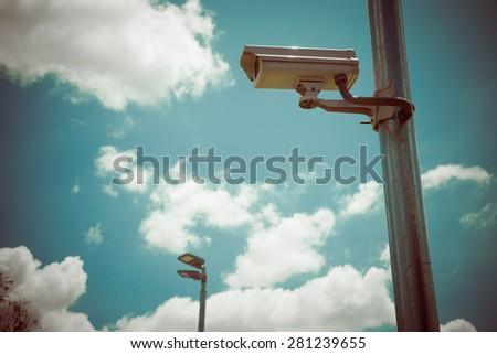 CCTV camera or Surveillance Operaiting on Blue Sky, process color  - stock photo