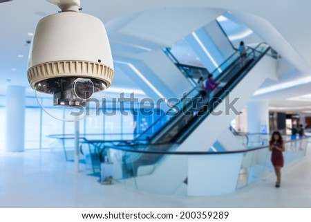 CCTV camera or surveillance operating in glass building - stock photo