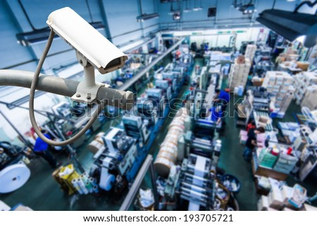 CCTV Camera or surveillance operating inside industrial factory - stock photo