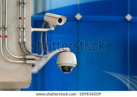 CCTV camera or surveillance operating on blue wall background - stock photo