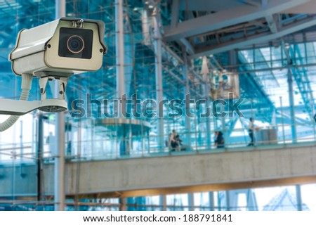 CCTV camera or surveillance operating with electric door in back - stock photo