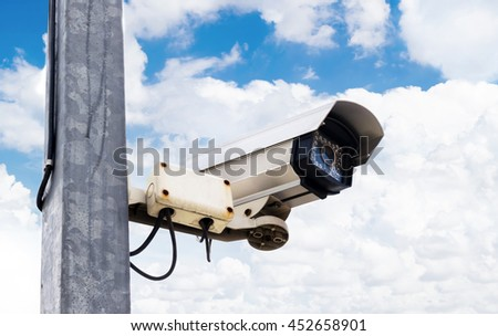 CCTV cameras on poles in public areas. In the background of blue sky and clouds.
