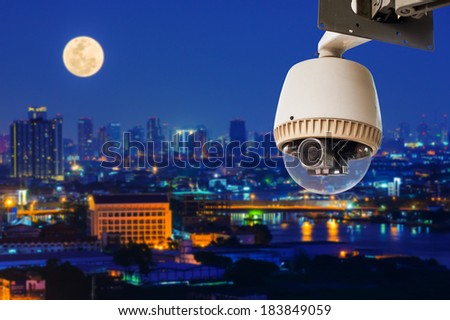 CCTV or surveillance operating with city in background - stock photo