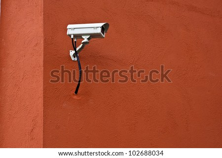 CCTV security camera and red wall.