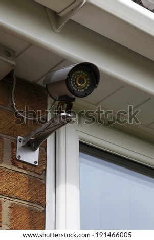 CCTV security camera for home protection, privacy, safety, security against crime & surveillance, mounted on house exterior wall.