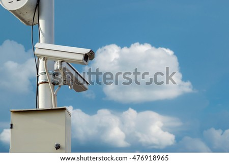 CCTV security camera isolated on blue sky background.