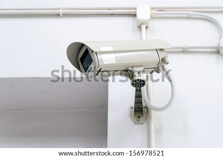 CCTV security camera mounted on the wall - stock photo