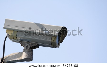 cctv security camera on a blue sky background showing signs of weathering - stock photo