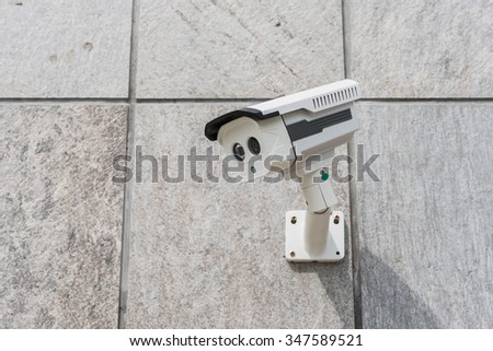 CCTV security camera on stone wall pattern - stock photo