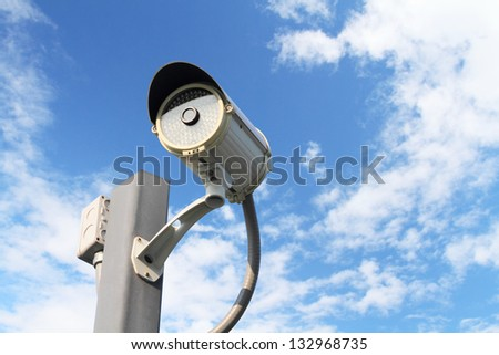 CCTV, security camera with cloudy sky - stock photo