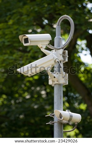 CCTV security cameras in front of green trees - stock photo
