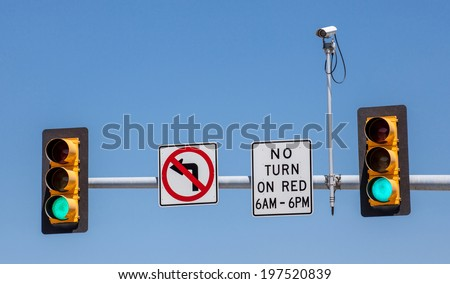 CCTV, Surveillance security camera with the traffic light and sign against a blue sky - stock photo