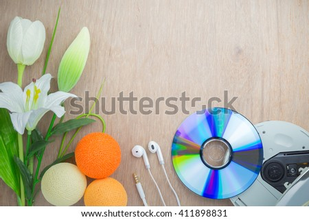 CD and player/ earphones/ flowers with copy space on wood background - stock photo