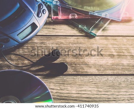 CD player with disc and earphones on wooden plank under warm light - stock photo