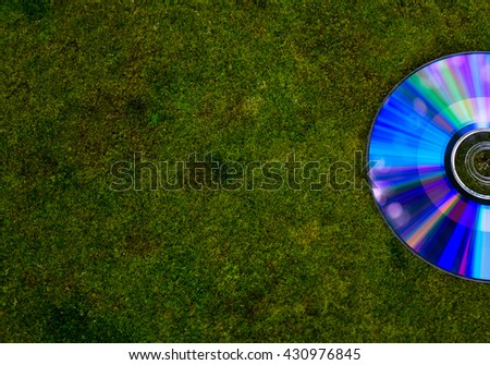 CD sfalte wet and green, bright moss. Green moss, asphalt, and a CD with highlights. - stock photo