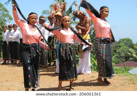 CECER VILLAGE, INDONESIA-APR.21: Women perform a traditional dance in costume for tourists visiting the Cecer Village on Flores Island, Indonesia on April 21, 2014. - stock photo