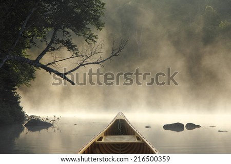 Cedar Canoe Bow on a Misty Lake - Ontario, Canada - stock photo