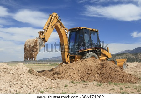 Cedar City, UT, USA - April 5, 2012: A backhoe digs an irrigation trench for an agricultural field.