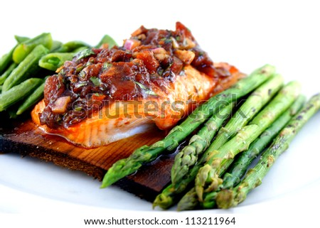 Cedar planked salmon served under roasted tomato vinaigrette and accompanied by sugar snap peas and blistered asparagus.