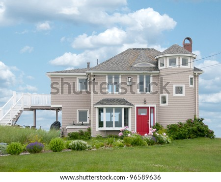 Cedar shakes house with a bright red door sits on the Atlantic Seacoast near Kennebunkport, Maine. - stock photo