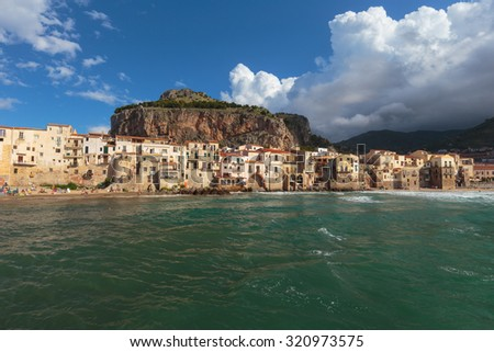 CEFALU, ITALY - SEPTEMBER 20 2015: Coastal Town and Tourist Location Cefalu at the sea of the island of sicily. Warm summer day with mediterranean houses at the beach and stormy sky