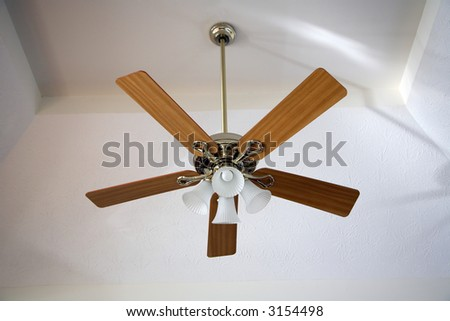 Ceiling fan hanging from a vaulted ceiling. - stock photo