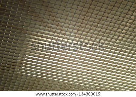 Ceiling fixture grid with light shining through - stock photo