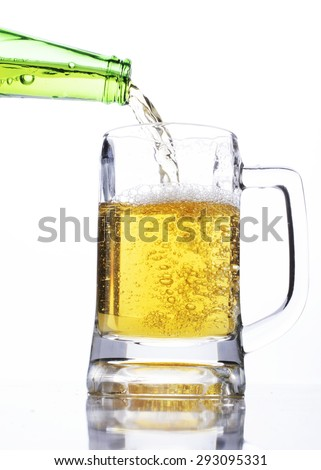 Celebrate beer days concept with pouring beer into a glass on white background - stock photo