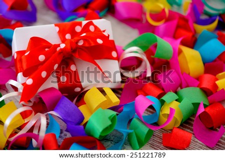 Celebrating a special day. Top view image of multicolored confetti as a frame for a gift box with red ribbon placed on wooden table - stock photo