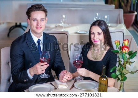 Celebrating a wedding anniversary together. Romantic dinner in the restaurant. Young loving couple visits a restaurant and raised their glasses of wine and smotrtya into the camera holding hands - stock photo
