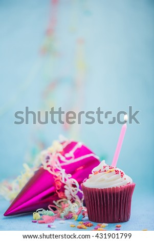 celebrating birthday with cupcake and candle on blue background - stock photo