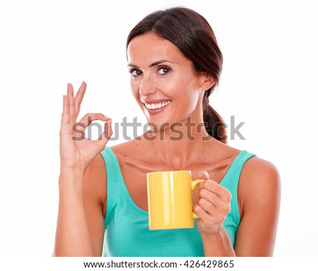 Celebrating brunette woman with coffee mug looking at camera gesturing a perfect sign wearing a green tank top and her long hair tied back isolated - stock photo