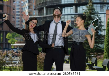 Celebrating business success. Three confident and motivated business partners are happy about of business project. All are wearing formal suits. Outdoor business concept - stock photo