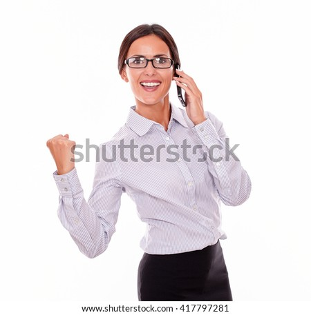 Celebrating businesswoman speaking on cell phone while looking at camera and making a gesture of victory with one hand an wearing her straight hair back and a button down shirt on a white background - stock photo