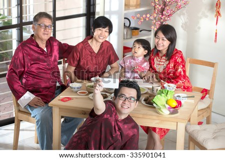 Celebrating Chinese New Year, reunion dinner. Happy Asian Chinese multi generation family with red cheongsam selfie while dining at home. - stock photo