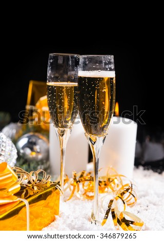Celebrating Christmas and the New Year with two glasses of romantic champagne standing on snow with burning advent candles and luxury golden gifts, dark background with copyspace