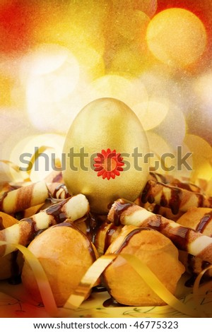 Celebrating Easter with decorated golden egg and chocolate profiteroles. Over festive bokeh lights.