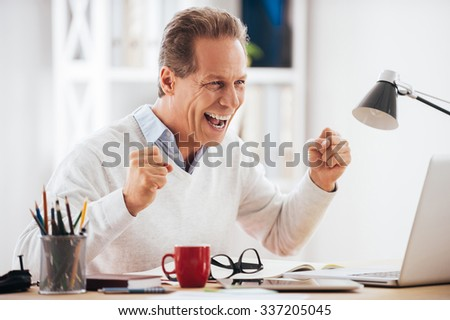 Celebrating success. Happy mature man looking at his laptop and gesturing while sitting at his working place - stock photo