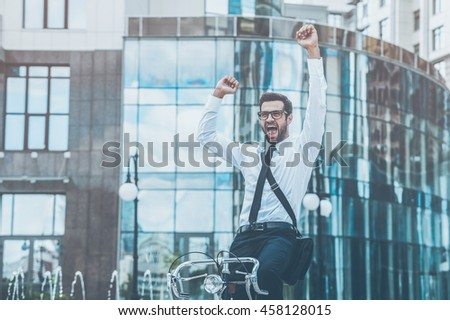 Celebrating success. Low angle view of cheerful young businessman keeping arms raised and expressing positivity while riding on his bicycle
