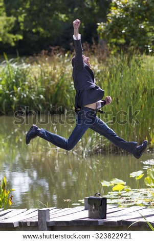 celebrating success outdoors concept - energetic businessman jumping with arm raised up with strength for ambition and promotion on bridge near water,natural summer daylight - stock photo