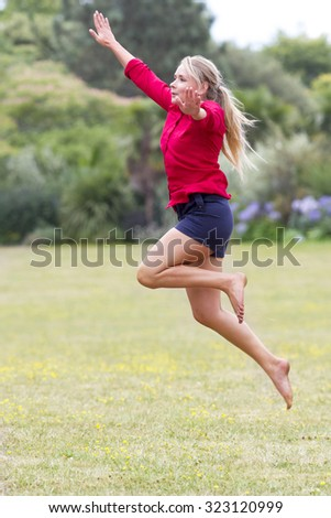 celebrating success outdoors concept - happy beautiful young woman in shorts jumping high with arms raised for freedom and happiness in city park,natural summer daylight