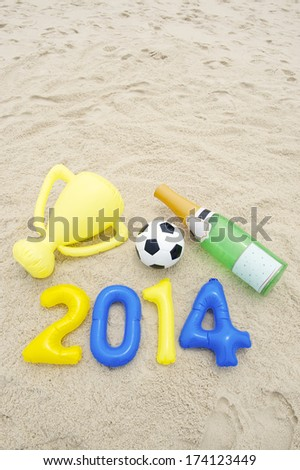 Celebrating 2014 winning with soccer ball football, inflatable trophy, and champagne bottle - stock photo