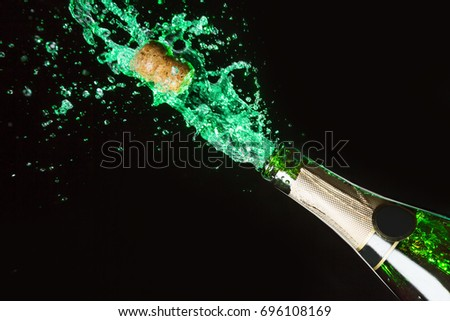 Celebration alcohol theme with explosion of splashing green absinth on black background