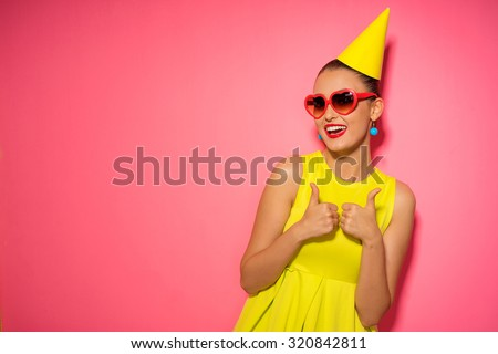 Celebration and party. Having fun. Young pretty woman in yellow dress and birthday hat is laughing. Colorful studio portrait with pink background. - stock photo