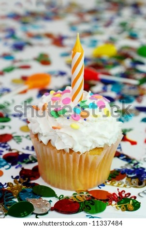 Celebration cupcake with candle and sprinkles.  Confetti and suckers in background.