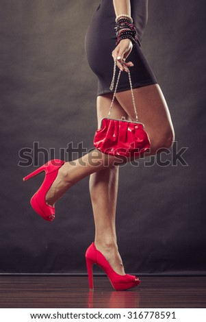Celebration disco and evening fashion concept. Woman in black short dress red spiked shoes holding handbag bag, part of body female legs in high heels on party floor